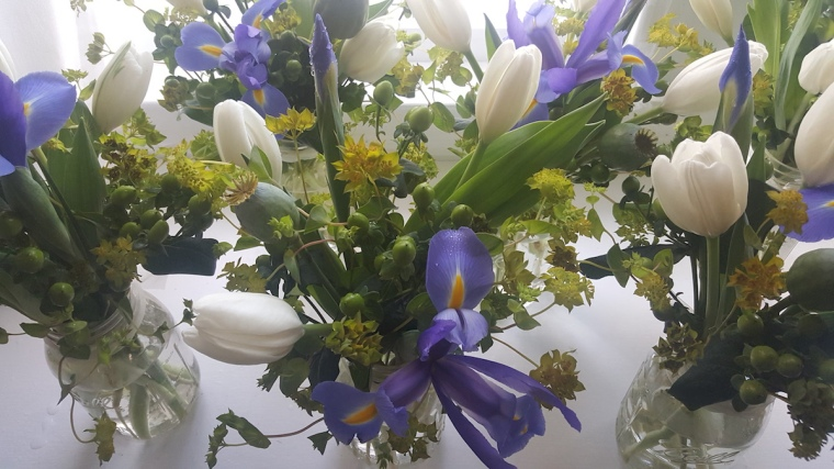 Simple centerpieces of tulips, irises and poppy pods for a joint Mother's Day/First Communion luncheon.