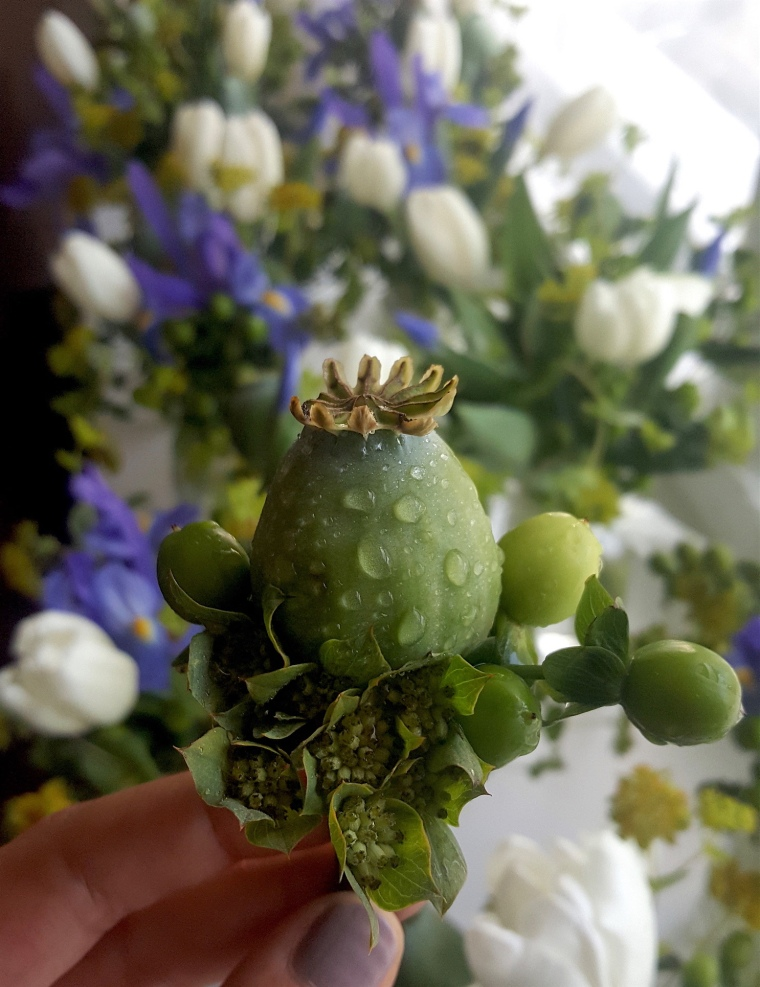Little boy's boutonniere made from a poppy pod and hypercium berries for a First Communion.