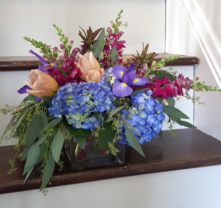 A low, table top arrangement with blue hydragenas, snap dragons, irises and seeded eucalyptus for CLE Baby event.